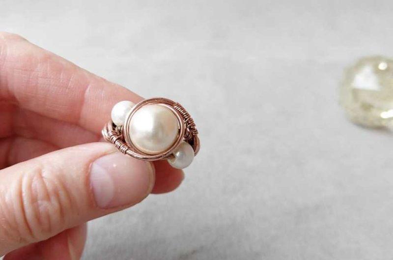 золотое кольцо с жемчугом в руке